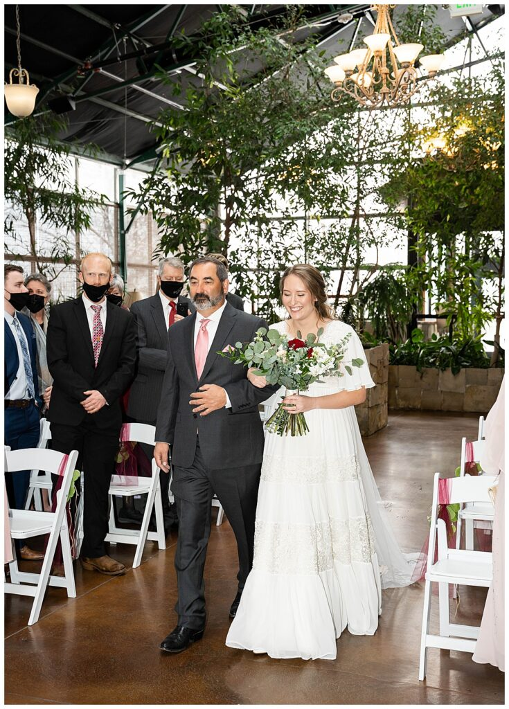 bride and father walking down the isle during indoor ceremony